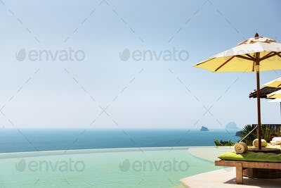 infinity pool with parasol and sun beds at ocean