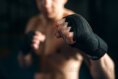 Muscular male person in black bandages