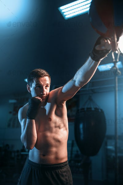 Boxer in bandages training with bag in gym