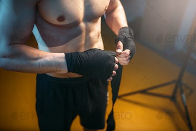 Muscular male person hands in black bandages