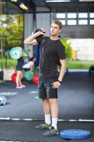 Confident Athlete Carrying Kettlebell In Health Club