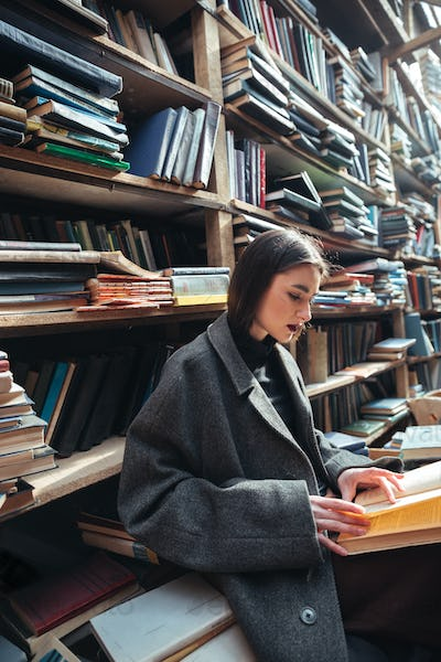 Portrait of a woman reading book in an old library