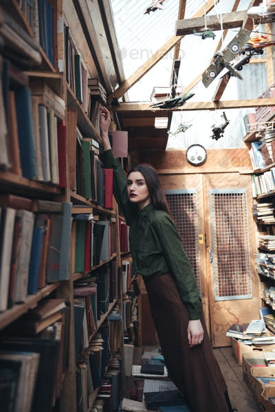 Side view of woman taking book from shelf
