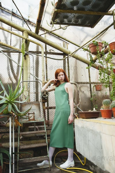 Young pensive girl standing in greenhouse