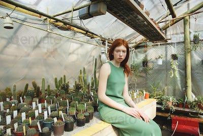 Girl sitting on shelf with cacti