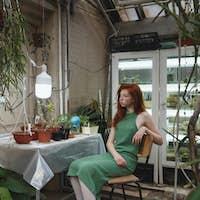 Girl sitting on chair among plants