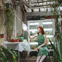 Girl sitting near table in greenery and looking at lamp