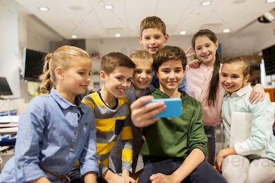 group of school kids taking selfie with smartphone
