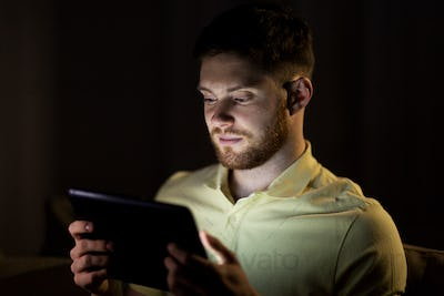 young man with tablet pc computer at night