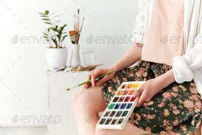 Cropped picture of young caucasian lady painter
