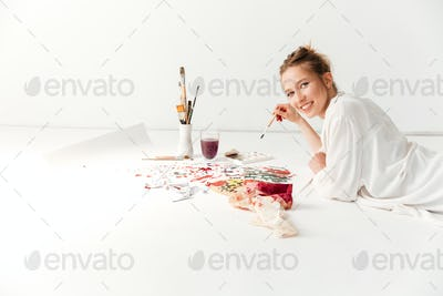 Happy young caucasian lady painter at workspace