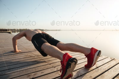 Portrait of a healthy young man doing push ups