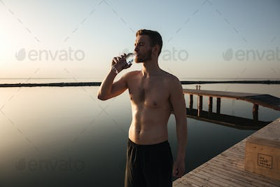 Portrait of a young tired sportsman drinking water after jogging