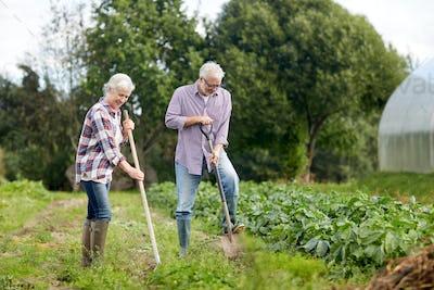senior couple with shovels at garden or farm