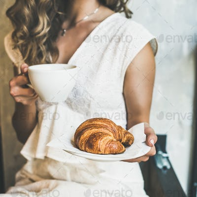 Blond woman holding croissant and cappuccino in cafe, square crop