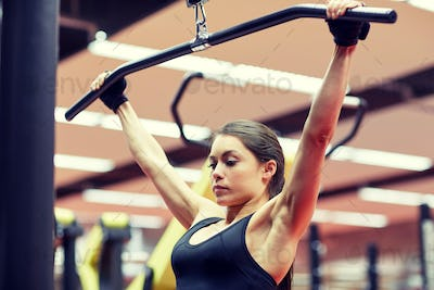 woman flexing arm muscles on cable machine in gym