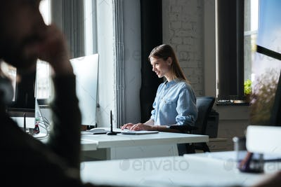 Woman work in office using computer. Looking aside.