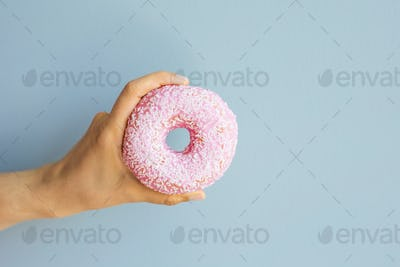 Woman holding pink delicious donut on blue background