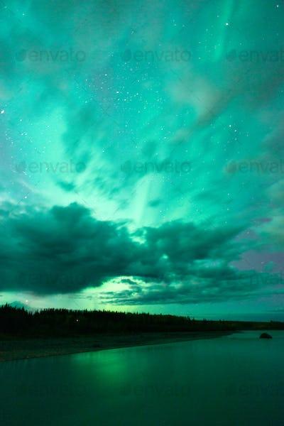 Lake Reflects Aurora Borealis Emerging Through Clouds Remote Alaska