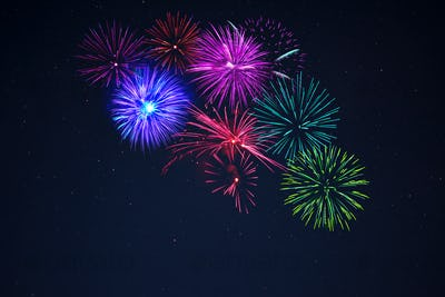 Pink purpe blue green fireworks over starry sky