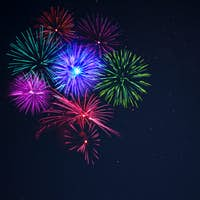 Pink purpe blue green fireworks over night sky