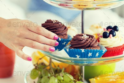 close up of hand taking cupcake from cake stand