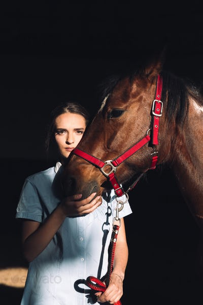Amazing young girl sitting outdoors hugging her horse
