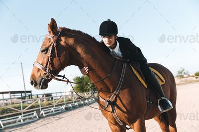 Concentrated young lady sitting on her horse.