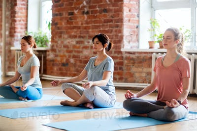 group of women making yoga exercises at studio