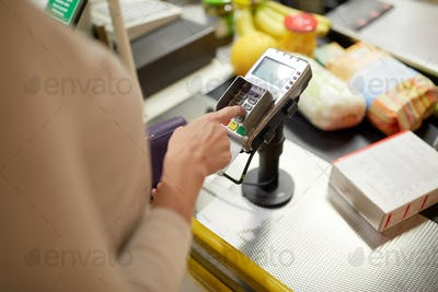 woman entering pin code at store cash register