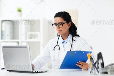 doctor with laptop and clipboard at hospital