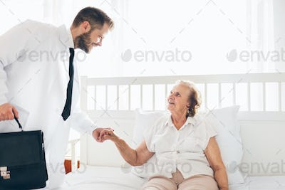 Providing care for elderly. Doctor visiting elderly patient at home.