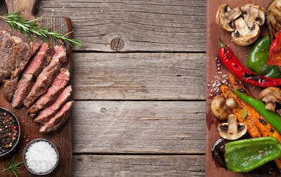Beef steak and grilled vegetables on cutting board