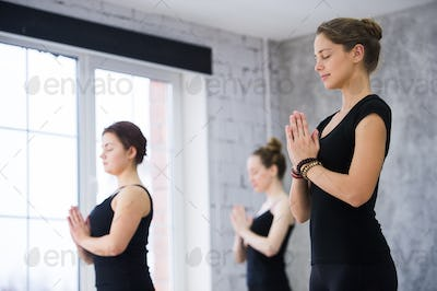Female trainer with class standing in namaste pose at yoga class