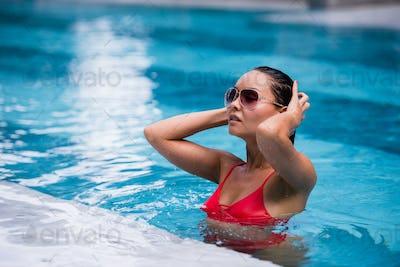 Tenned beautiful asian woman in orange bikini and sunlasses sitting in swimming pool. Fashionable