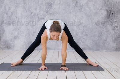 A sportive young girl stretching legs, yoga class. Blonde woman sitting in twine