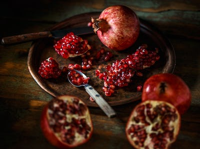 Pomegranate seeds in a metal spoon