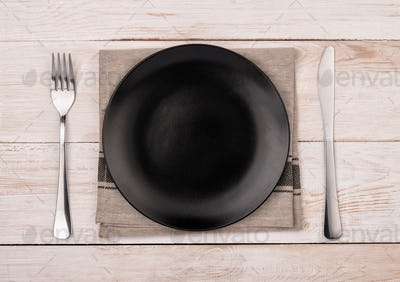 Top view of empty black  plate, silverware and napkin