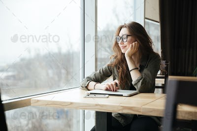 Woman with laptop looking in window
