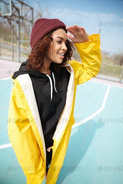 Happy african curly young woman wearing yellow coat walking