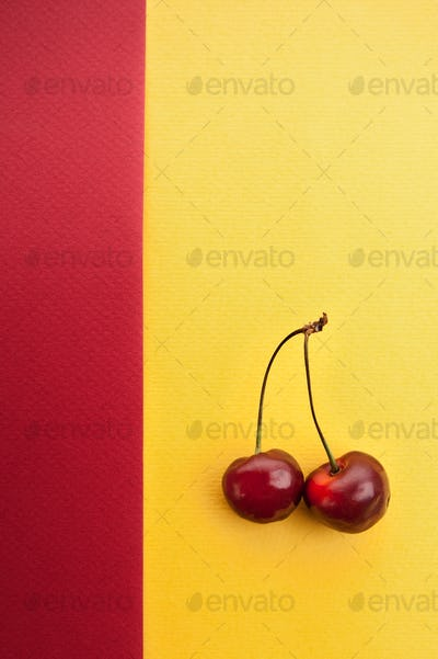 Cherry on a red-yellow textured background with a place for your