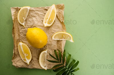 Lemons on kraft paper on a light green textured background.