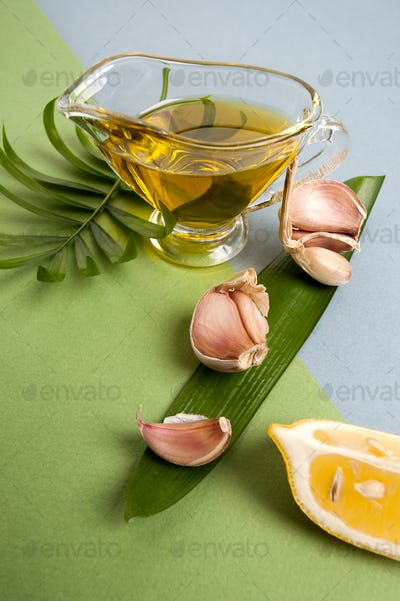 Fresh garlic, lemon slices and olive oil on a blue-green texture