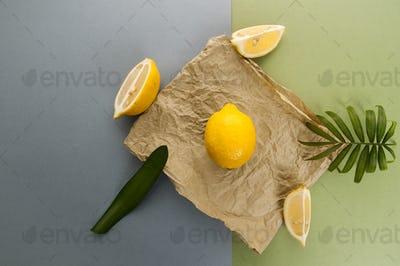 A minimalistic composition with limonomas and green leaves on a
