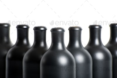 Set of empty black clay bottles on a white background close-up.