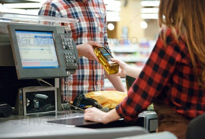 Man standing near cashier's desk in supermarket.