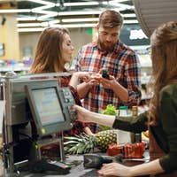 Concentrated young couple standing in supermarket