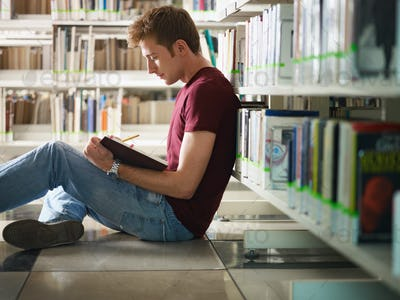 Young College Student Reading Book Sitting On Floor In Library