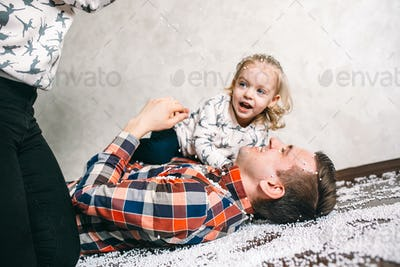 Dad plays with his daughter on the floor