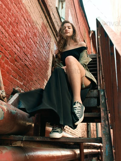 fashionable young female sit on steel stairs